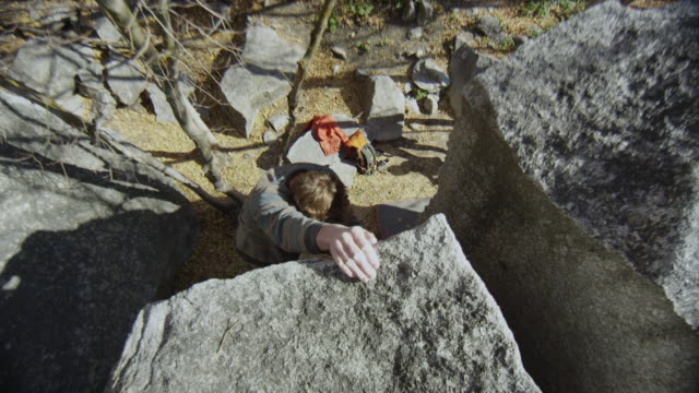 stockvideo's en b-roll-footage met top down view of as man climbs up boulder reaching the top - boulder rock