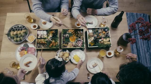 vídeos y material grabado en eventos de stock de vista de arriba hacia abajo de la familia japonesa comiendo osechi ryori en nochevieja - table top view