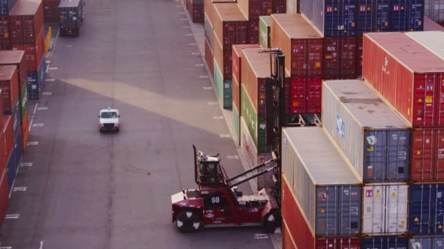 top handler arranging containers in yard at port of long beach - aerial view - container stock videos & royalty-free footage