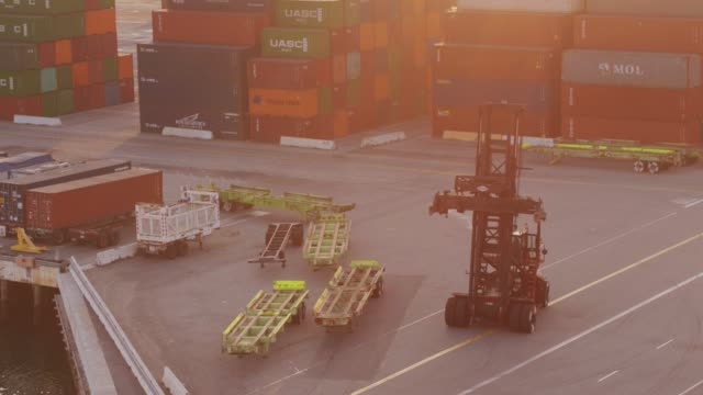 top handler driving along waterfront in container port - aerial shot - unloading stock videos & royalty-free footage