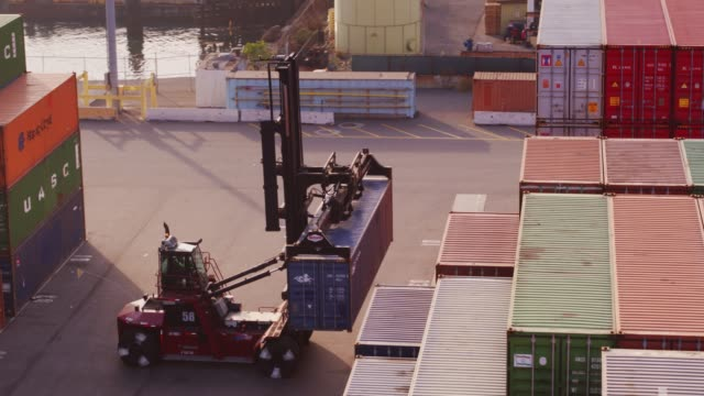 top handler removing cargo container from stack - aerial - port of los angeles stock videos & royalty-free footage