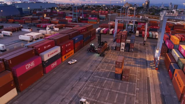 top handler working in container yard at twilight - aerial - port of los angeles stock videos & royalty-free footage