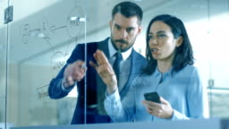 Top Manager and Female Executive Outlining Company Optimization Plan on a Glass Blackboard, Drawing with Market and Using Smartphone while Standing in the Modern Glass and Concrete Office.