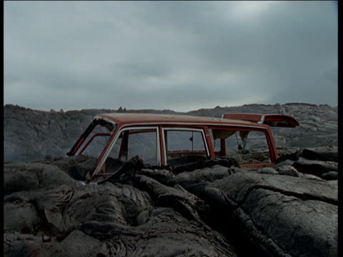 top of burnt out car buried in cooling lava field, hawaii - misserfolg stock-videos und b-roll-filmmaterial
