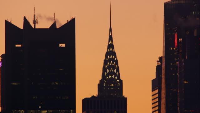 vídeos de stock e filmes b-roll de top of chrysler building lit up against a bright orange sky at at dusk in nyc - prédio chrysler