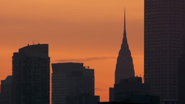 vídeos de stock e filmes b-roll de top of chrysler building peeking out from behind other skyscrapers against an orange sky. - prédio chrysler