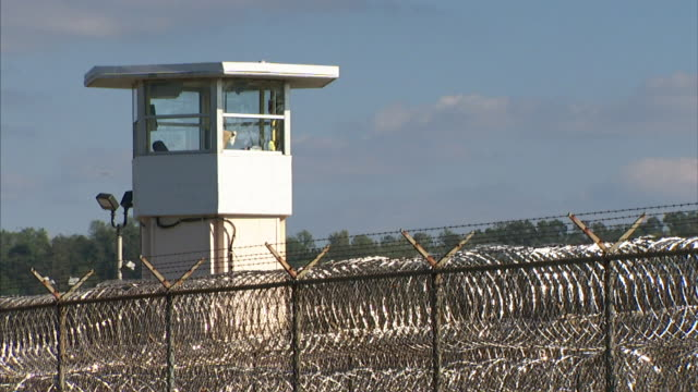 Top of guard tower w/ looped razor wire on fencing FG Incarceration incarcerated maximum security secure prison not jail correctional facility