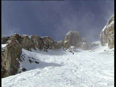 Top of Jackson Hole Mountain pan right to snow covered mountain and rocky ridges with snow swirling in the air