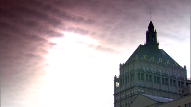 top of kodak tower w/ company name on roof, cirrocumulus clouds moving across sky w/ sun light shining through. industry, industrial, manufacturing,... - cirrocumulus stock videos & royalty-free footage