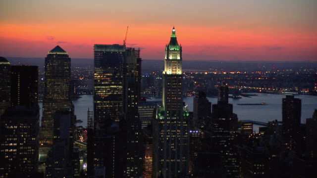 aerial top of lighted woolworth building against a red and orange sunset, and the river beyond / new york city, new york, united states - woolworth building stock videos & royalty-free footage