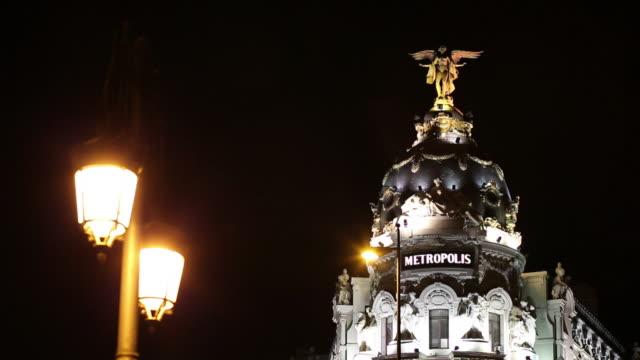 ms top of metropolis building illuminated at night / madrid, spain - マドリード グランヴィア通り点の映像素材/bロール