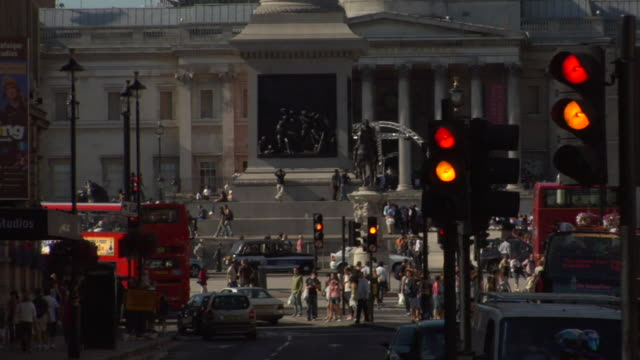 ms top of nelson's column/ td ws traffic and pedestrians passing through trafalgar square/ london, england - nelson's column stock videos and b-roll footage