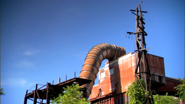 top of rusted metal building w/ huge curved piping, s curve from roof under raised platform next to structure. midwest, rust belt, foundry, closed,... - rusty stock videos & royalty-free footage