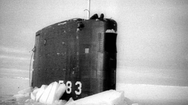 top of submarine uss spargo seen poking through ocean of ice / two crew members on top of the visible spout / crew member walking away from sub... - toccare con un dito video stock e b–roll