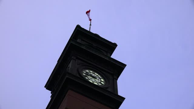 top of the clock tower and the flag of canada on the no. 8 hose station, toronto, canada - klocktorn bildbanksvideor och videomaterial från bakom kulisserna