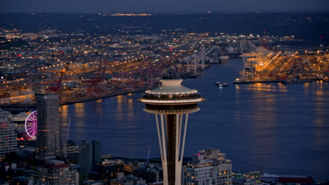 aerial top of the space needle with seattle in the background at night - seattle stock-videos und b-roll-filmmaterial