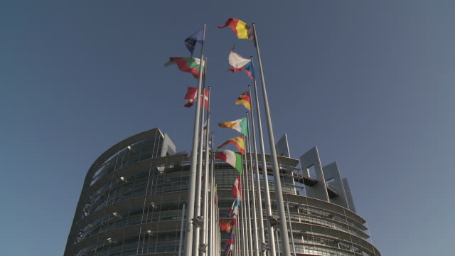 MS Top part of Louise Weiss European Parliament building with flags swaying  on breeze / Strasbourg, Alsace, France