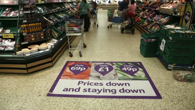 top shot customers push shopping carts across a floor promotion sign that reads prices down and staying down in the fruit and vegetable section of a... - tesco点の映像素材/bロール