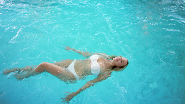 top shot of a sensual blonde women with long hair in her 30s swimming backstroke in a turquoise blue swimming pool, she is wearing a expensive white designer bikini while enjoying her me time in this warm thermal spring water – toothy smile in day spa