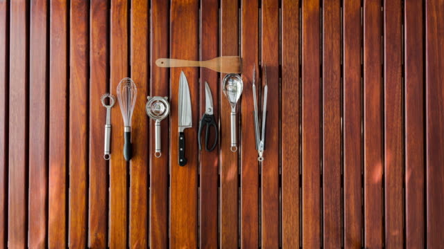 Top shot of cooking utensils appearing on a wooden table