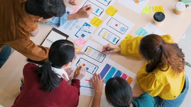 トップビューアジアのux開発者とuiデザイナーは、現代のオフィスでテーブルのカラーコード上のモバイルアプリインターフェイスワイヤーフレームデザインについてブレーンストーミング。 - プロトタイプ点の映像素材/bロール