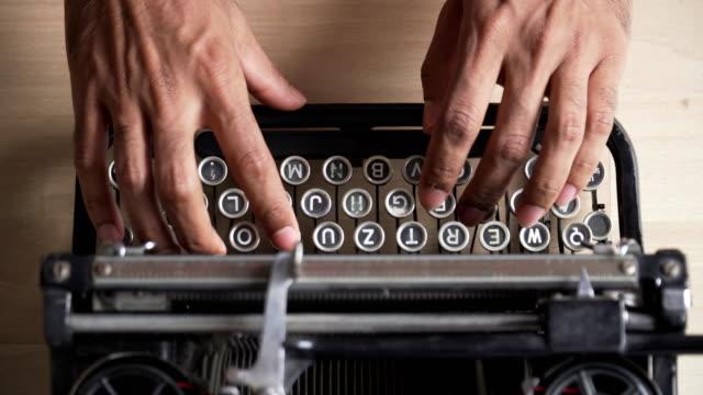 vidéos et rushes de vue de dessus: mains d'asiatique utilisent retro machine à écrire qui est clavier allemand - message