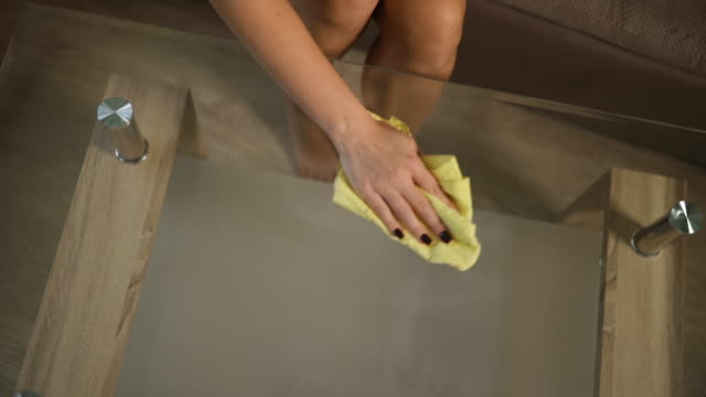 top view: bare blonde sits and cleans glass table top with yellow cloth at home - table top view stock videos & royalty-free footage