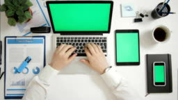 Top view businessman working on laptop at office desk with multiple greenscreen gadgets phone and tablet
