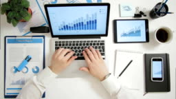 Top view businessman working on laptop computer with charts and graphs at office desk phone and digital tablet near