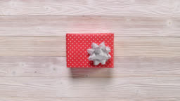 Top view christmas holiday gift boxes on wooden table, stop motion