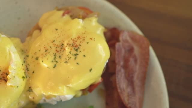 top view close up of knife and fork cutting eggs benedict and bacon - cooking pan video stock e b–roll