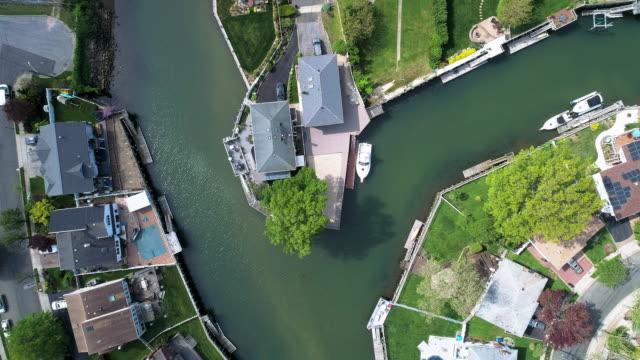 vidéos et rushes de vue de dessus, directement au-dessus de la vidéo de drone d'un canal à oceanside, new york city, avec des maisons avec des piscines sur les arrière-cours et les quais avec des bateaux le long du rivage. la caméra statique planant sur l'emplacement. - queens