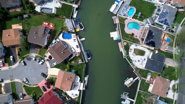 top view, directly above drone video of a channel in oceanside, new york city, with houses with pools on backyards and piers with boats along the shore. looking down camera with the panning motion along the channel. - long island stock videos & royalty-free footage