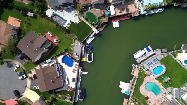 top view, directly above drone video of a channel in oceanside, new york city, with houses with pools on backyards and piers with boats along the shore. spinning and descending combined camera motion. - marina stock videos & royalty-free footage