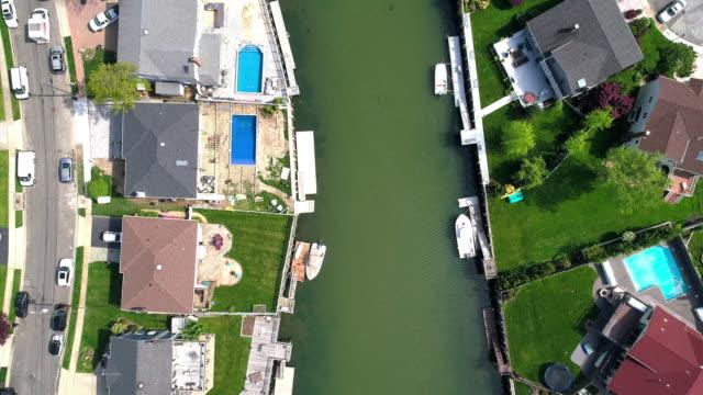 vidéos et rushes de vue de dessus, directement au-dessus de la vidéo de drone d'un canal à oceanside, new york city, avec des maisons avec des piscines sur les arrière-cours et les quais avec des bateaux le long du rivage. regardant vers le bas de la caméra avec le mouv - queens