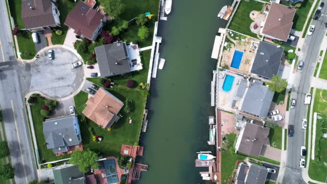 top view, directly above drone video of a channel in oceanside, new york city, with houses with pools on backyards and piers with boats along the shore. looking down camera with the panning motion along the channel. - marina stock videos & royalty-free footage