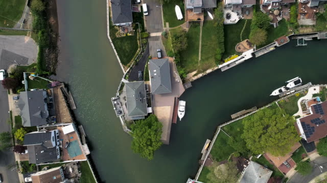 top view, directly above drone video of a channel in oceanside, new york city, with houses with pools on backyards and piers with boats along the shore. looking down camera with the panning forward motion along the channel. - vista marina stock videos & royalty-free footage