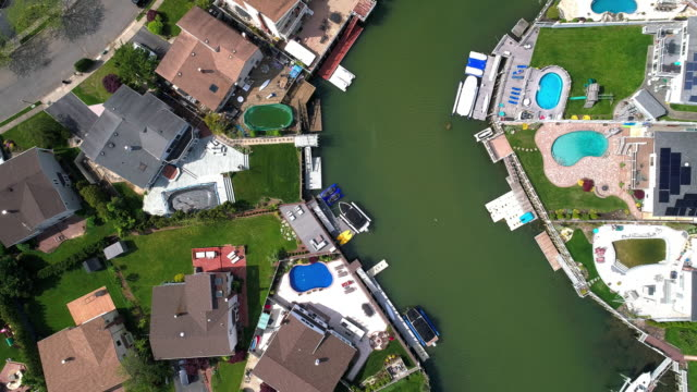top view, directly above drone video of a channel in oceanside, new york city, with houses with pools on backyards and piers with boats along the shore. spinning and descending combined camera motion. - standing water yard stock videos & royalty-free footage