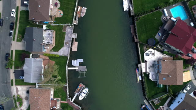 top view, directly above drone video of a channel in oceanside, new york city, with houses with pools on backyards and piers with boats along the shore. looking down camera with the panning forward motion along the channel. - nassau stock videos & royalty-free footage
