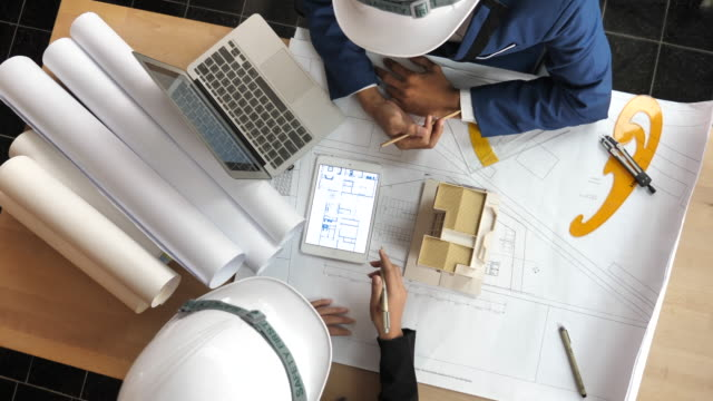 top view engineer and site manager looking at paper blueprint plans at a construction site. business concept for the teamwork of heavy industry - construction site stock videos & royalty-free footage