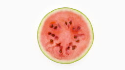 Top view from above of a half cut ripe watermelon slice. Cross section. Rotating on the turntable isolated on the white background. Close-up.