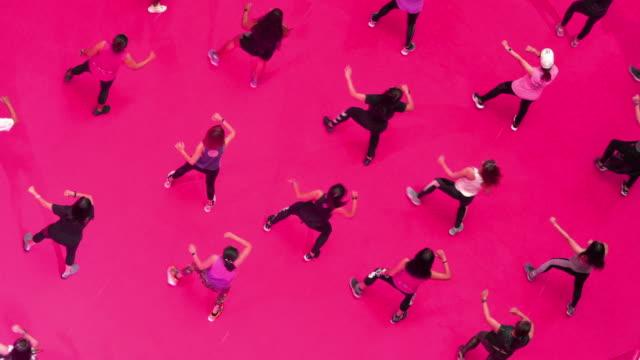 vidéos et rushes de groupe supérieur de vue des personnes dansant pendant la classe d'exercice sur le plancher rose - dancing