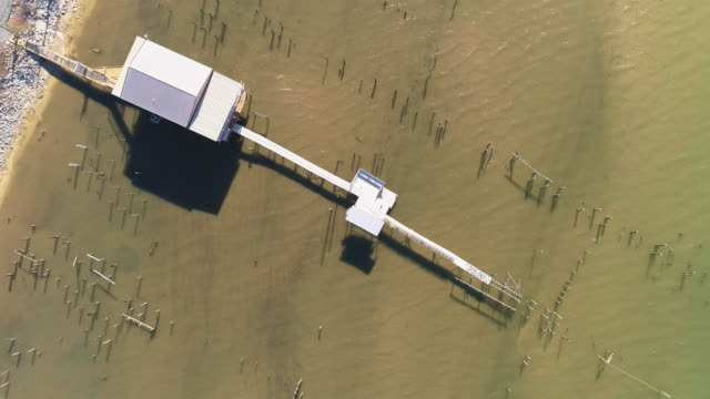 Top view, looking-down directly above view of the pier on the Lake Pontchartrain, New Orleans, Louisiana, USA. Aerial drone video with the descending camera motion.