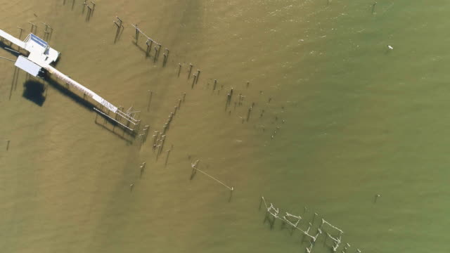 Top view, looking-down directly above view of the pier on the Lake Pontchartrain, New Orleans, Louisiana, USA. Aerial drone accelerated video with the panning camera motion.