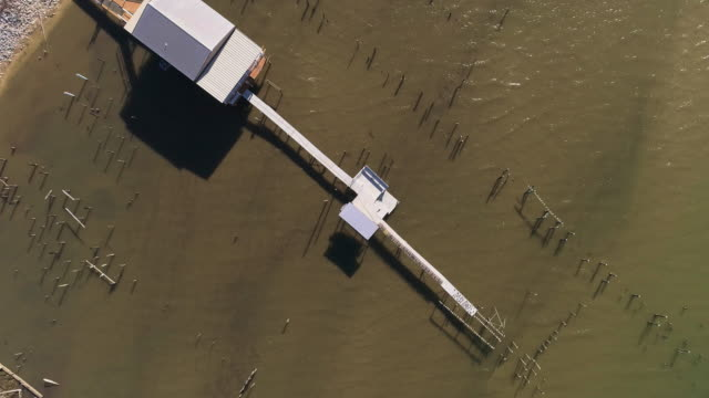 Top view, looking-down directly above view of the pier on the Lake Pontchartrain, New Orleans, Louisiana, USA. Aerial drone video with the ascending and spinning camera motion.