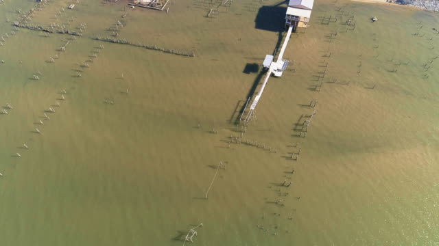 Top view, looking-down directly above view of the pier on the Lake Pontchartrain, New Orleans, Louisiana, USA. Aerial drone video with the cinematic slow forward and tilting-up camera motion.