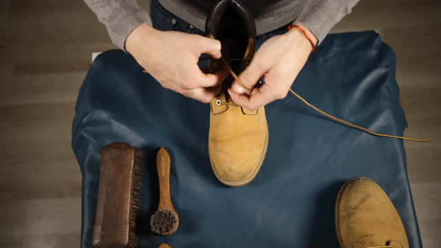 top view: male hands remove laces from yellow or beige boots - leather stock videos & royalty-free footage