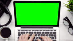 Top view male hands working on laptop computer with green screen at white desk from above