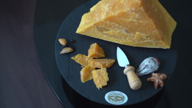 top view of a dark table filled with a wide variety of cheeses. - slice stock videos & royalty-free footage