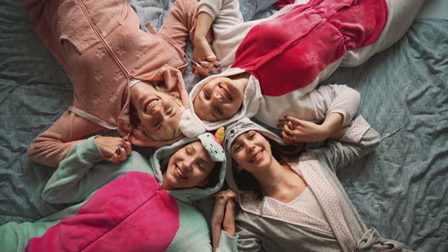 top view of a four girlfriends in nightwear lying in the bed and smiling - nightwear stock videos & royalty-free footage